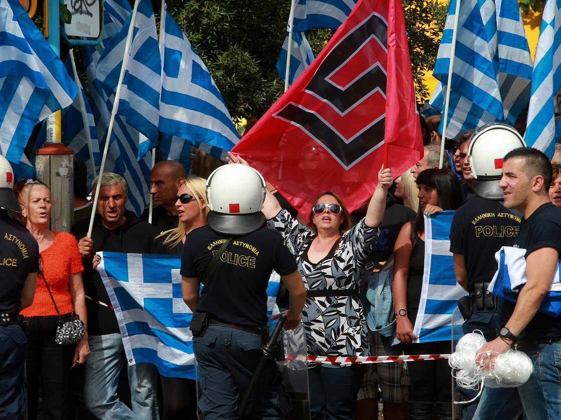 Supporters of the ultra-right-wing Golden Dawn Party wait outside the Athens courthouse for the transfer of party leader Nikolaos Michaloliakos to the prosecutor Wednesday. Four lawmakers from Greece's neo-Nazi party Golden Dawn have been indicted on charges of belonging to a criminal organization.
