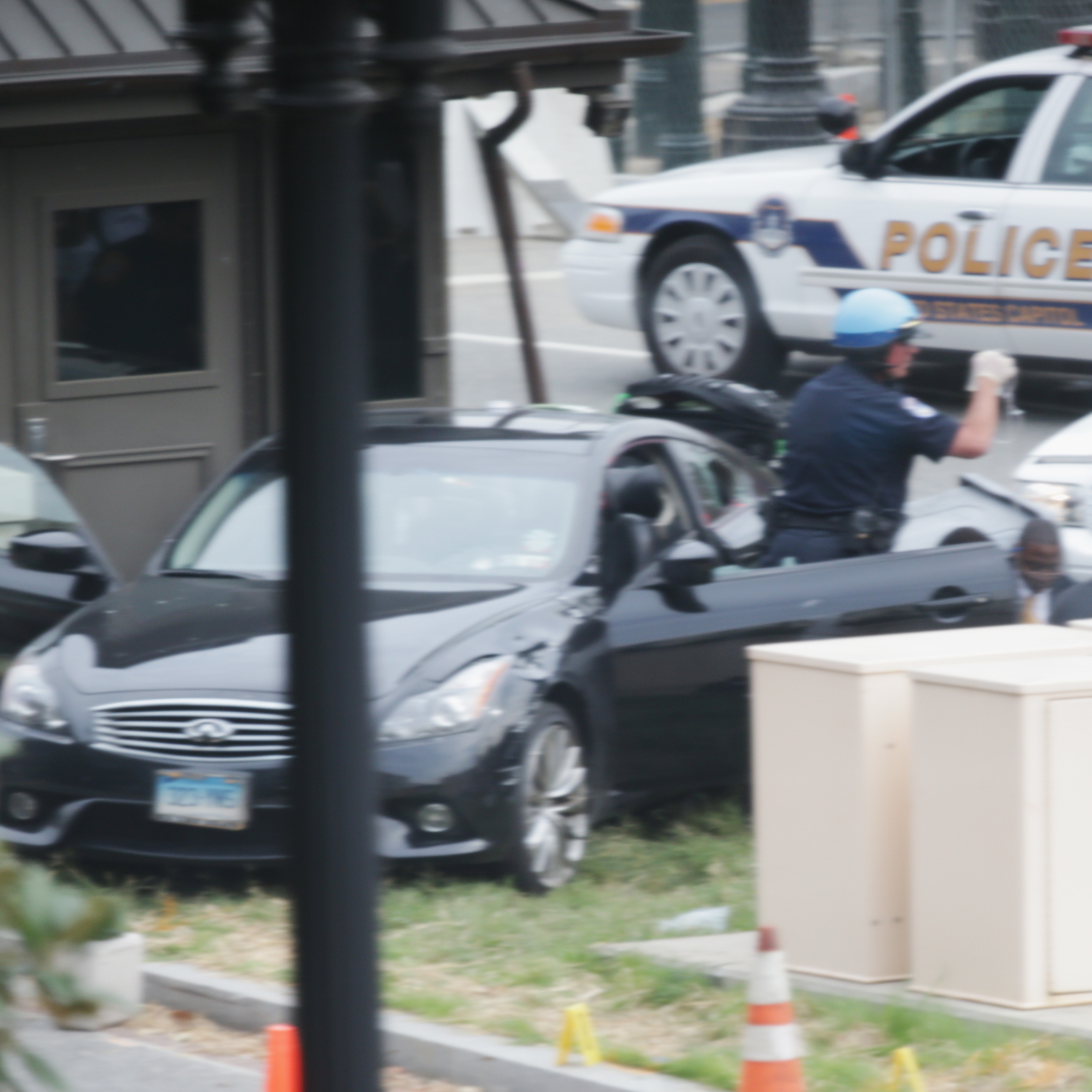 Police swarm around car on grass near the U.S. Capitol on Thursday. The suspect's black Infiniti is shown.