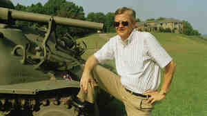 Tom Clancy poses next to a tank in his Maryland backyard. Though he never served in the military, his books were renowned for their detail.