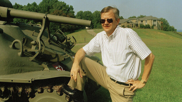 Tom Clancy poses next to a tank in his Mar