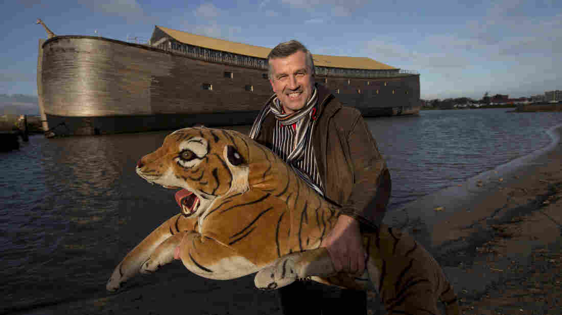 Johan Huibers poses with a stuffed tiger in front of the full-scale replica of Noah's Ark he built in the Netherlands.