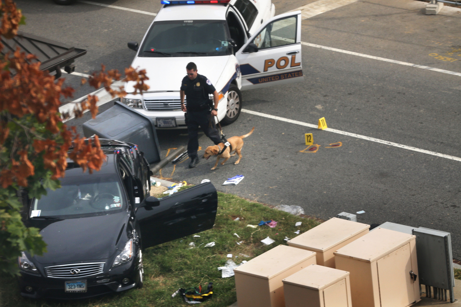 A police officer checks out a car on grass with his canine near the U.S. Capitol on Thursday in Washington, D.C. The Capitol and the White House were placed on lockdown after an 'active shooter' situation was reported.