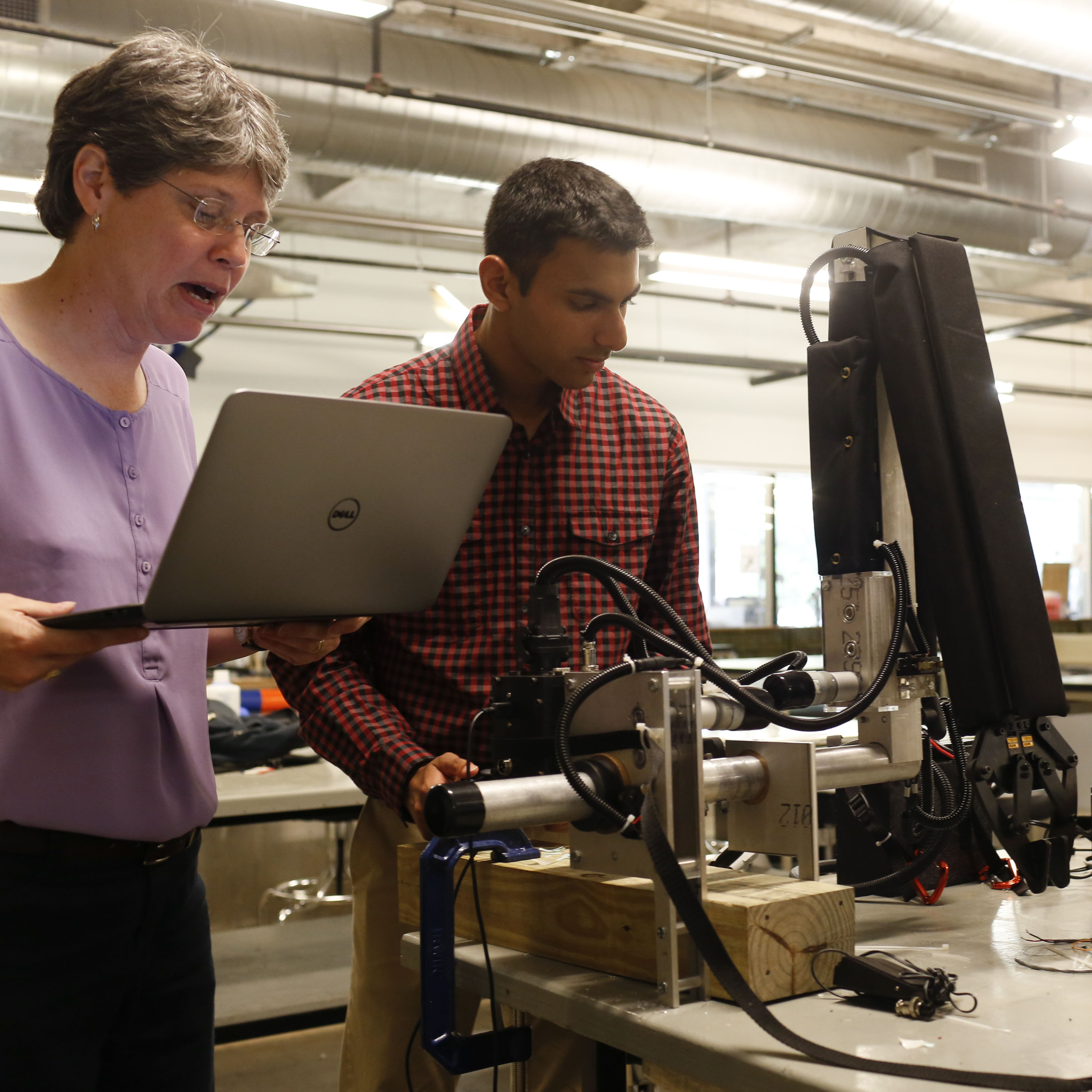 Ann Saterbak, a bioengineering professor at Rice University, reviews a list of improvements that were to be made to a robotic arm by undergraduate bioengineering students Nimish Mital (center) and Matthew Nojoomi.