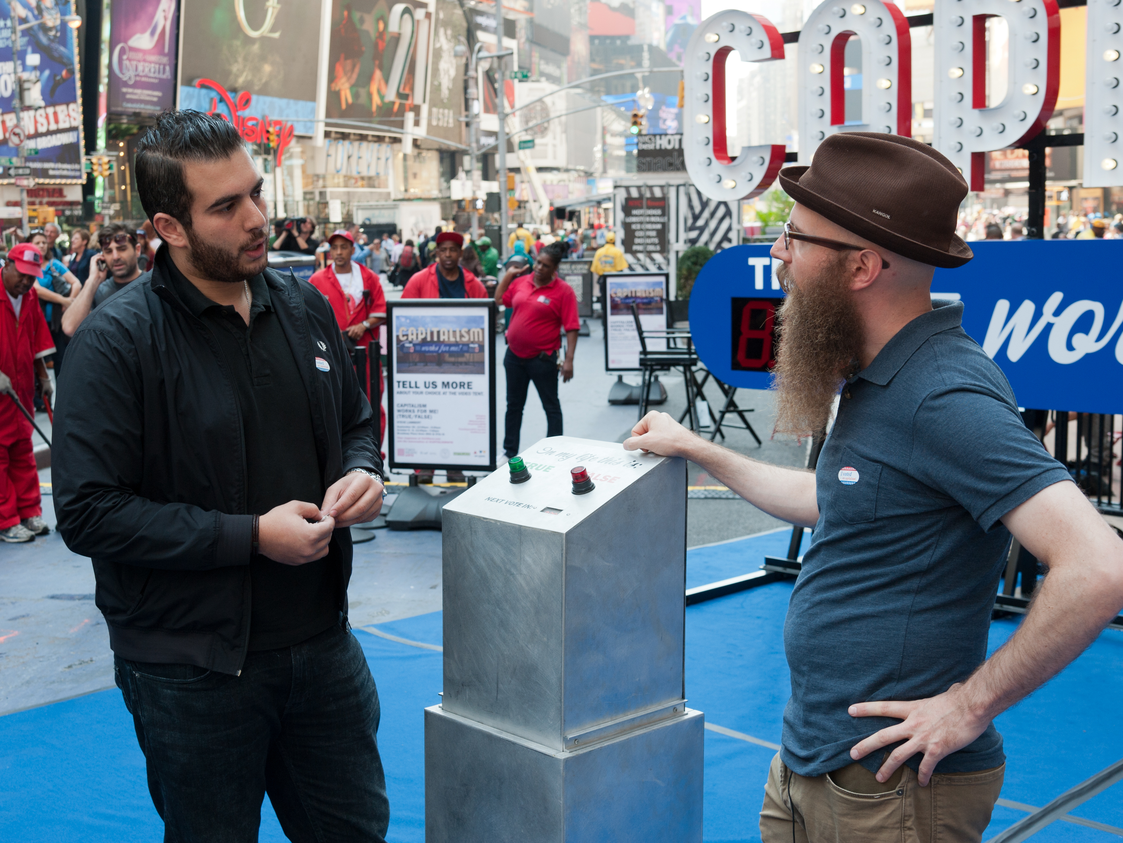 Artist Steve Lambert, right, asks people to vote on whether capitalism is working -- for them. The art installation is in Times Square through Oct. 9.
