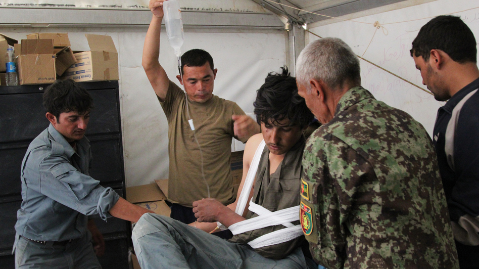 Afghan medics at Forward Operating Base Nolay in the southern province of Helmand treat an Afghan police officer shot by militants. (Sean Carberry/NPR)