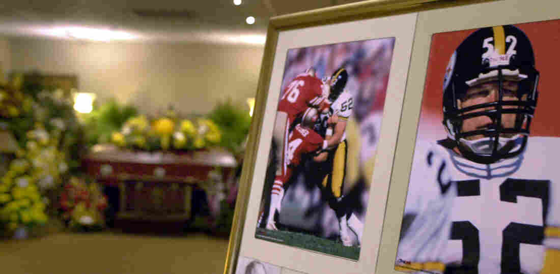 The casket bearing the body of former Pittsburgh Steelers center Mike Webster is surrounded by flowers, after funeral services in Pittsburgh in September 2002. Mark Fainaru-Wada and Steve Fainaru, authors of League of Denial, point to Webster's autopsy as one of the most significant moments in the history of sports.