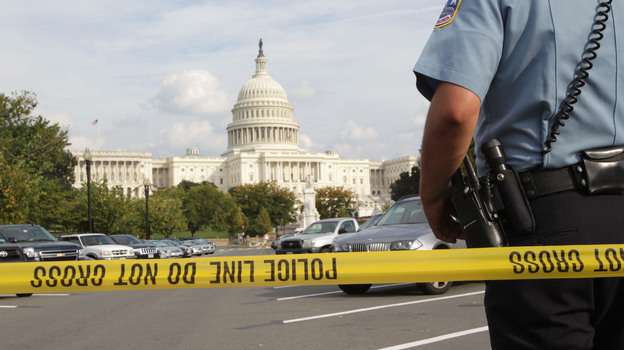 An officer stands just outside police tape Thursday as authorities investigate a car chase that began at the White House and ended near the Capitol. (Xinhua/Landov)