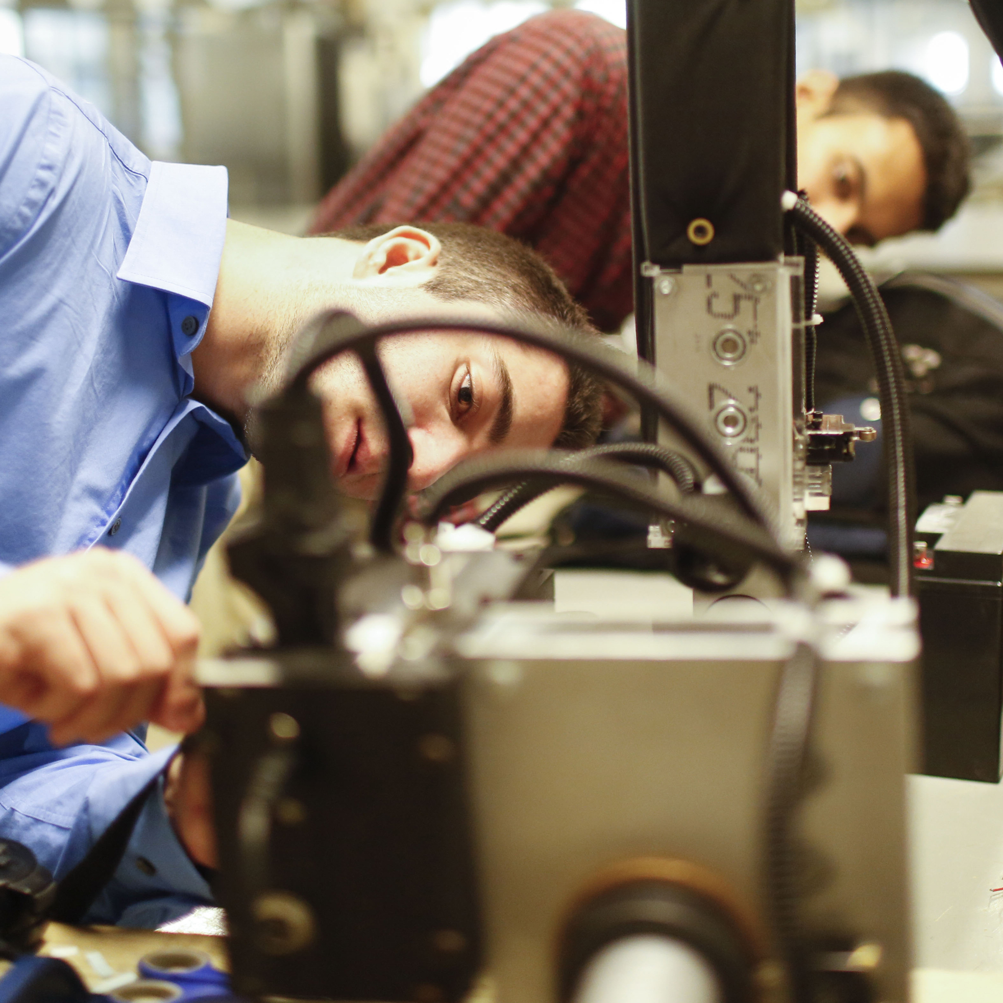 """We hit a ton of roadblocks,"" says team member Sergio Gonzales. Above, Matthew Najoomi (left) and Nimish Mital work on the robotic arm in a lab at Rice University."
