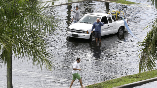 Workers pump water from the parking lot of the Dadeland Plaza shopping center on Thursday after heavy rains triggered by Tropical Storm Karen in Pinecrest, Fla., a suburb of Miami.