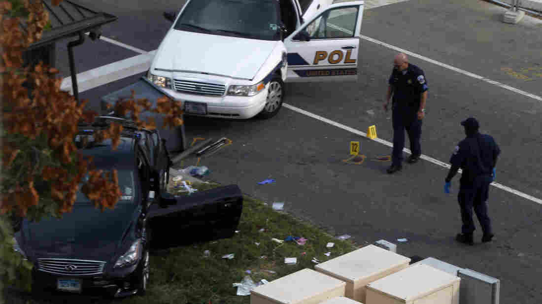 """Officers on Capitol Hill look at a car following Thursday's shooting, which left Miriam Carey, 34, dead. """"We're still very confused as a family why she's not still alive,"""" Carey's sister says."""