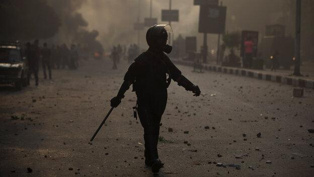 An Egyptian riot policeman moves into