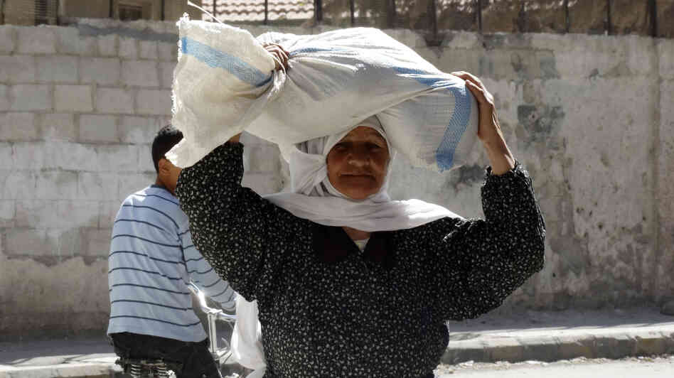 A woman carries a sack of food aid on her head in Ghouta, Syria, earlier this month.
