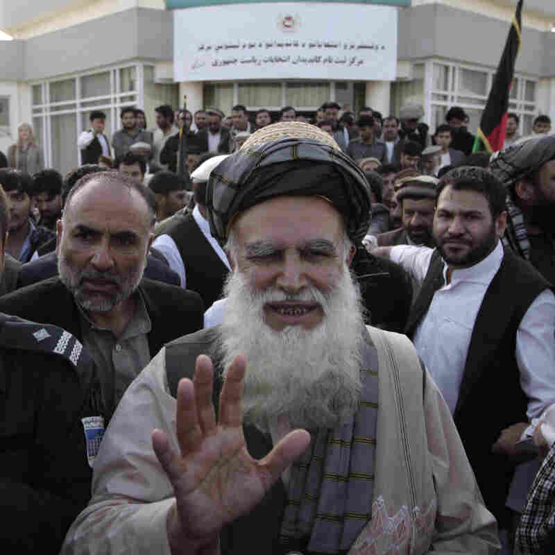 Abdul Rab Rasoul Sayyaf, an influential lawmaker and religious scholar, waves at his supporters on Oct. 3, after registering his candidacy in next year's presidential election.