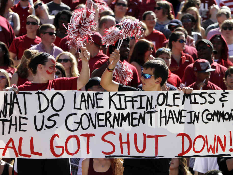 Alabama fans hold up a sign about the government shutdown during the first half of an NCAA college footbal