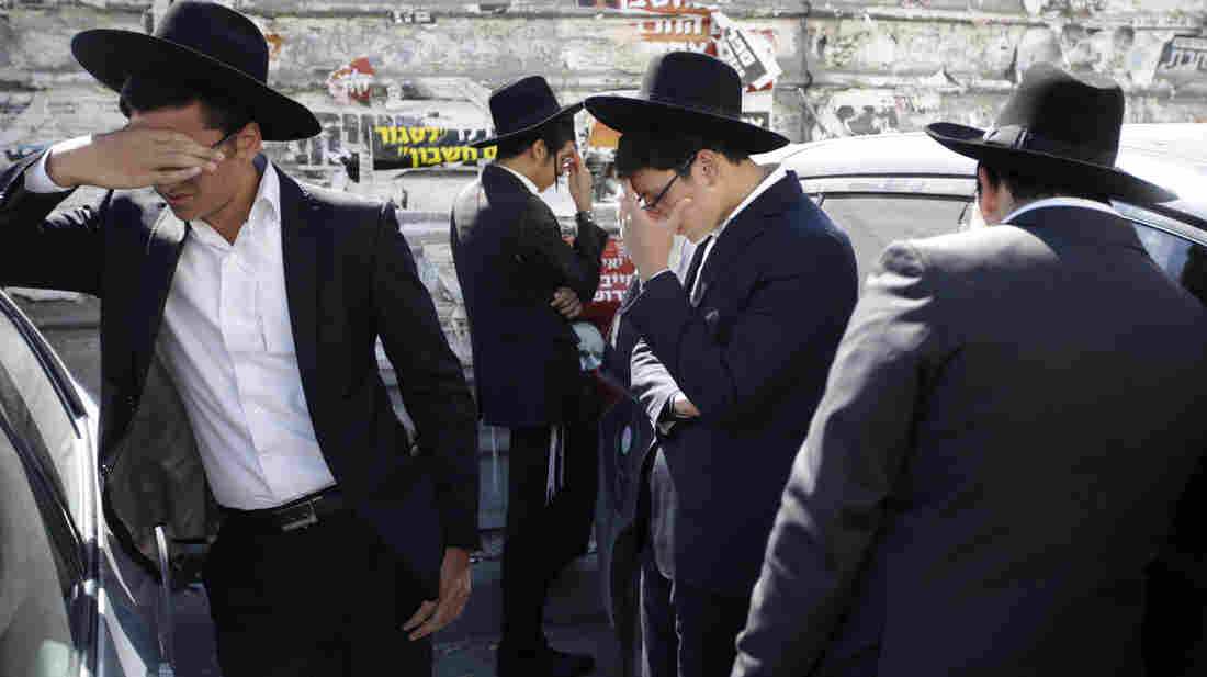 Followers of Rabbi Ovadia Yosef mourn outside his home in Jerusalem on Monday. The rabbi, who transformed his downtrodden community into a powerful force in Israeli politics, died at age 93.