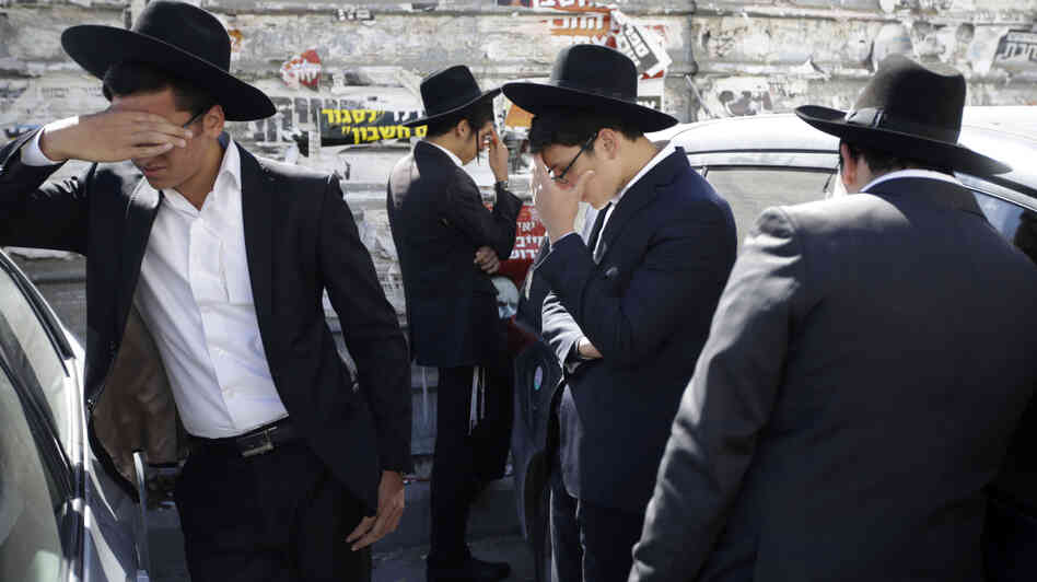 Followers of Rabbi Ovadia Yosef mourn outside his home in Jerusalem on Monday. The rabbi, who transformed his downtrodden community into a
