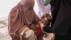 Avez, 2, is held by his mother, as he receives the polio vaccine in the Khyber Tribal Region in northwest Pakistan.