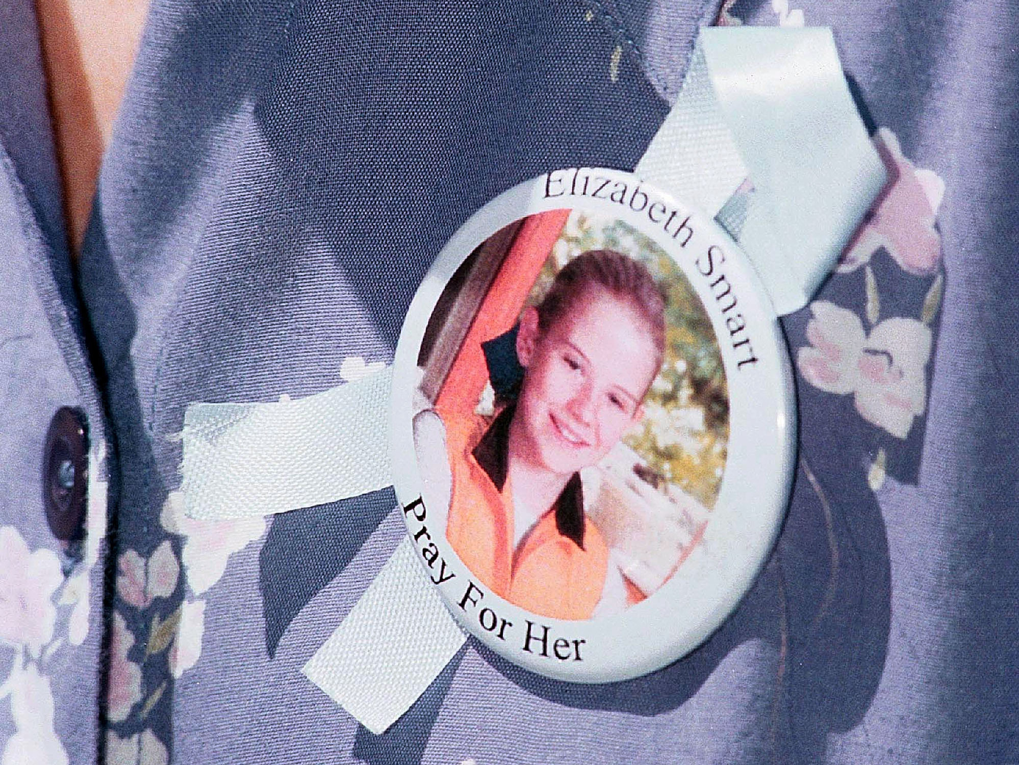 Elizabeth Smart's aunt, Cynthia Smart-Owens, wears a button of her niece during a news conference in June 2002, days after Smart had been abducted.