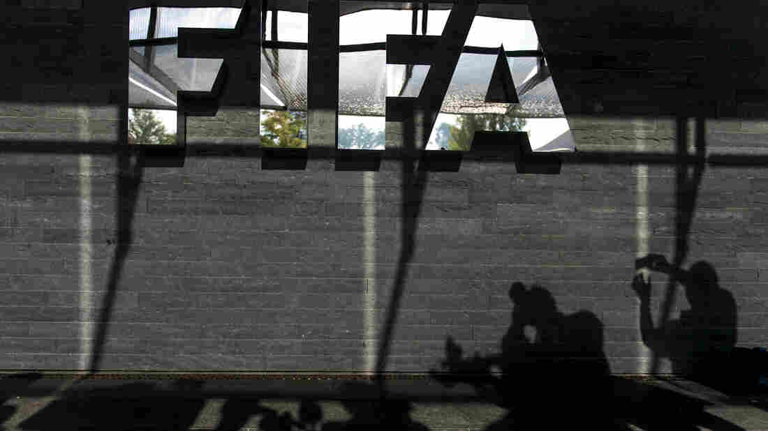 Shadows of journalists are seen next to a FIFA logo after a recent press conference on controversy swirling around 2022 World Cup construction projects in Qatar.
