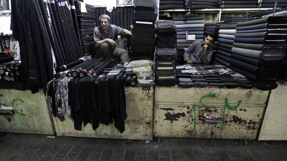 Two Iranian textile merchants wait for customers in Tehran's main bazaar. President Hassan Rouhani has raised hopes by reaching out to the West and promising to work for an end to sanctions. But his team has cautioned that the country's economic problems have deep roots.
