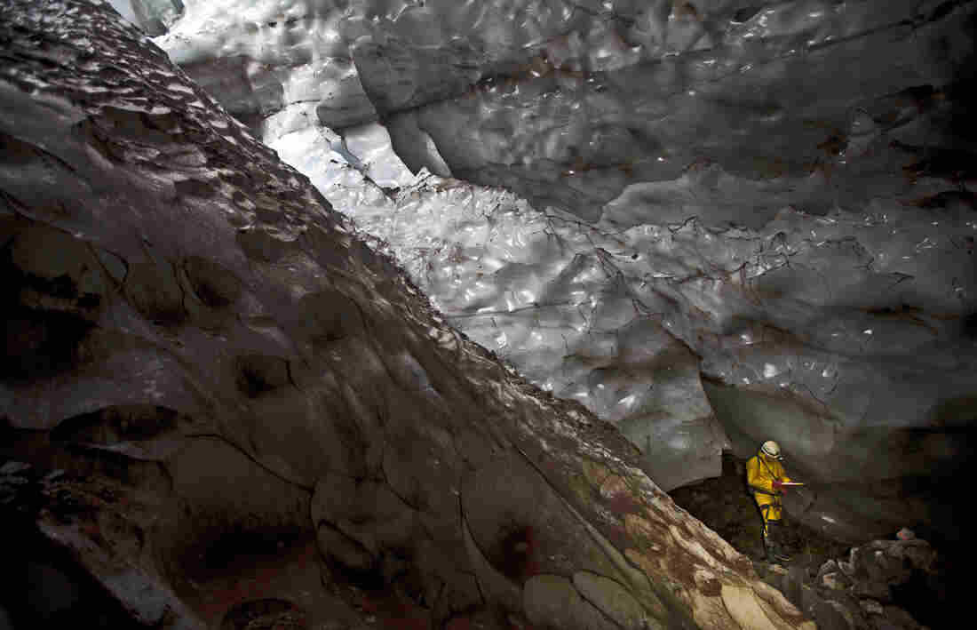 Mapping another world: An explorer writes down survey data in a glacier cave on Mount Hood.
