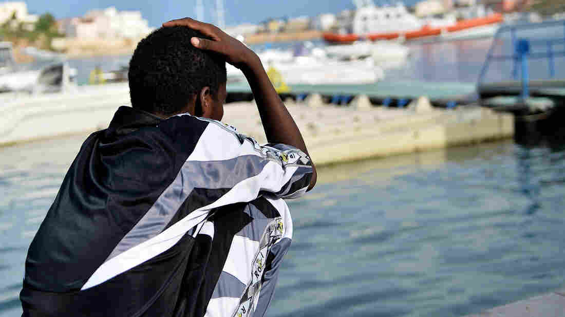 A survivor of the shipwreck of migrants off the Italian island of Lampedusa looks out over the water Tuesday. The tragedy has bought fresh questions over the thousands of asylum-seekers who arrive in Europe by boat each year.