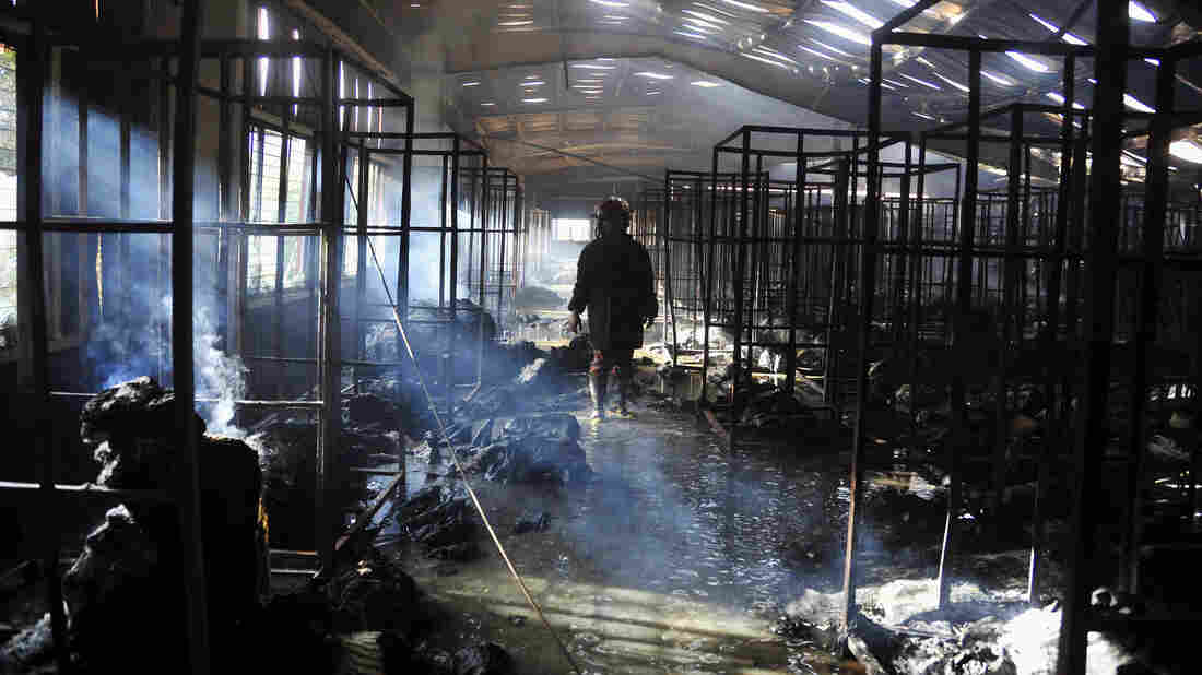 A Bangladeshi firefighter stands inside a damaged garment factory after it caught fire in Gazipur outside the capital