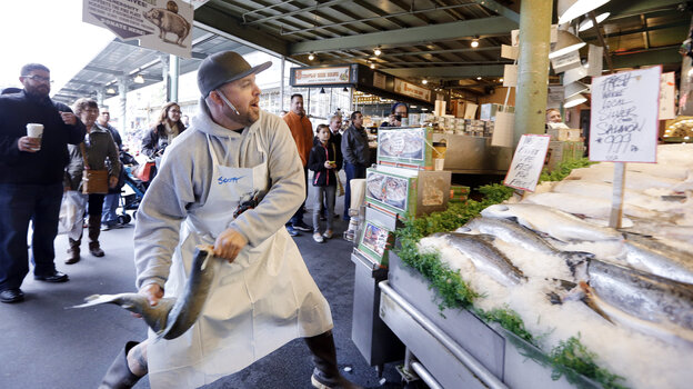 A fishmonger tosses a just-purchased fresh salmon to a colleague behind the counter at the Pike Place Fish Market in Seattle.