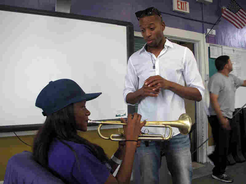 Trombone Shorty explains breathing technique to trumpet student Jazz Henry, a junior in the Warren Easton marching band.
