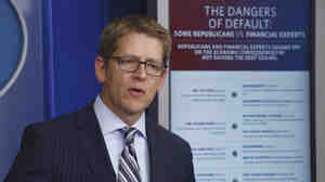 White House press secretary Jay Carney uses a visual aid comparing what Republican lawmakers said against what financial leaders said as he briefs reporters at the White House Thursday.