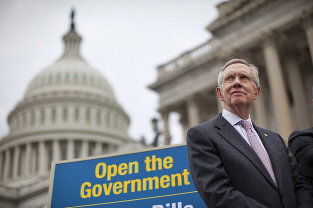 Senate Majority Leader Harry Reid (D-Nev.) and a sign of the times.