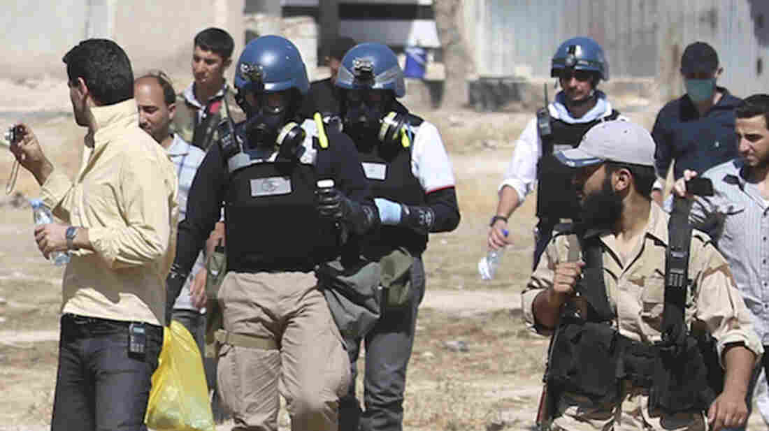 U.N. chemical weapons experts carry samples collected on Aug. 28 from a site of an alleged chemical weapons attack near the Syrian capital Damascus. The Organization for the Prohibition of Chemical Weapons, which is dismantling Syria's chemical weapons stockpile, was awarded the 2013 Nobel Peace Prize on Friday.