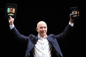 Amazon CEO Jeff Bezos holds up the Kindle Fire HD in two sizes during a press conference in Santa Monica, Calif., in September 2012.