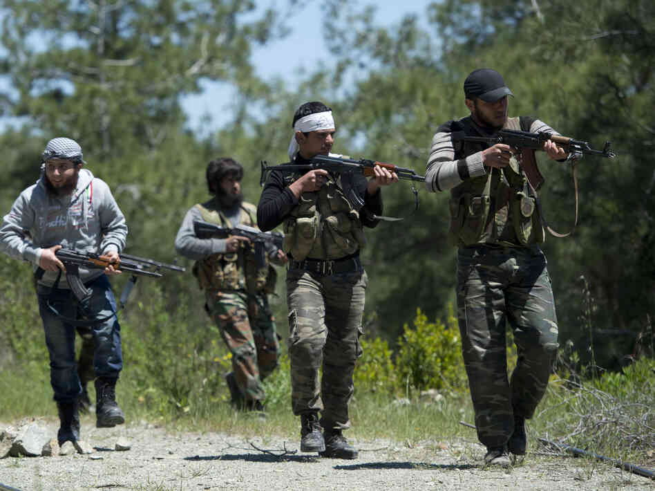 Rebel fighters from the Al-Ezz bin Abdul Salam Brigade train at an undisclosed location near the al-Turkman mountains in Latakia province, Syria, in April.