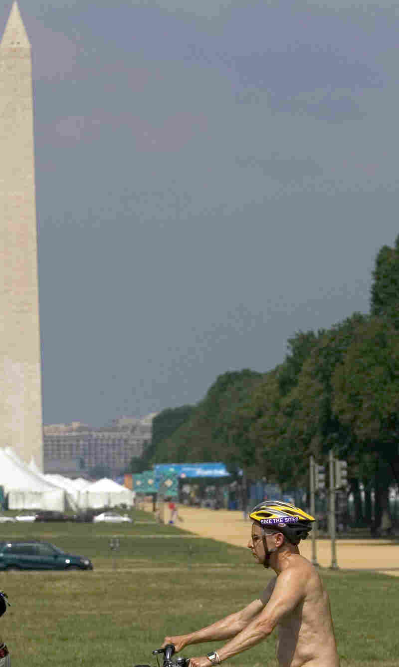 A demonstrator glides past the Washington Monument, as prelude to the World Naked Bike Ride on June 9, 2007.