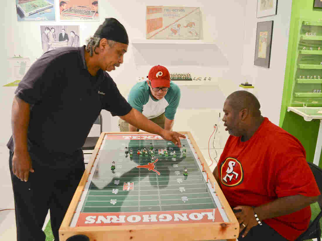 Kelvin Lomax (from left), Chris Bopst and Dru Sparks study the electric football field before a play. Their pastime of choice is on display at a museum in Richmond, Va.