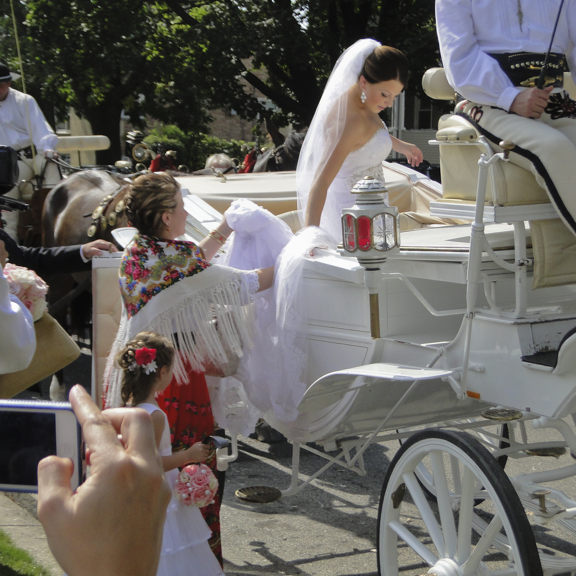 The bride's sister helps her into a carriage after the couple receives their blessings. Renee Stella Zieba and Michael John Livernois were married in Chicago.
