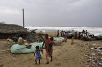 A woman leaves the Bay of Bengal coast with her children in the Ganjam district of Odisha, India.