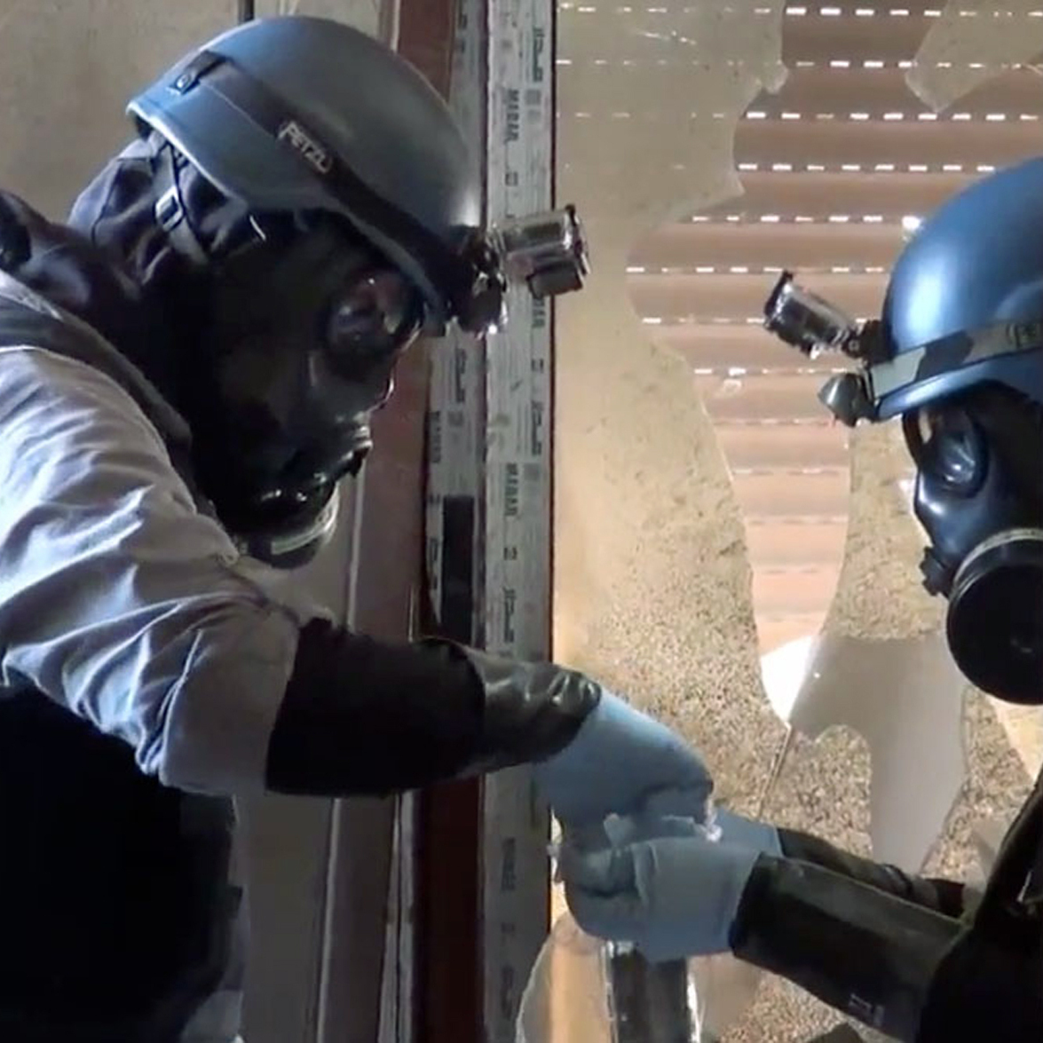 Members of a chemical weapons investigation team take samples outside Damascus on Aug. 29.