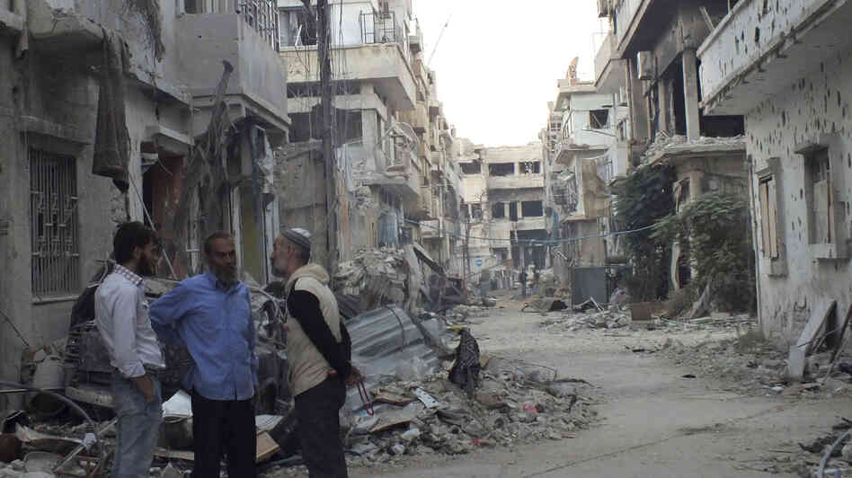 Men chat Thursday in front of badly damaged buildings in the central city of Homs. Many Syrians are critical of the Nobel Peace Prize that was announced Friday for the group that is in Syria to dismantle its chemical weapons program.