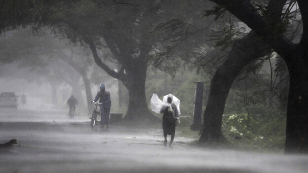 A man covers himself with a plastic sheet as a shield as he walks to a safer place near Gopalpur in eastern India Saturday. Hundreds of thousands of people living along India's eastern coastline took shelter from the massive powerful cyclone Phailin.