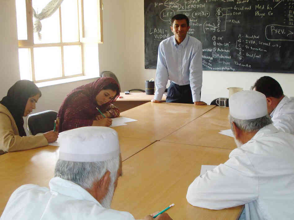 Dr. Dilip Joseph, standing, teaches medical personnel in Afghanistan.