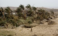 A woman returns to the cyclone-hit Arjipalli village on the Bay of Bengal coast in Orissa state, India, on Sunday. The state's Chief Minister Naveen Patnaik says that a full recovery will be a