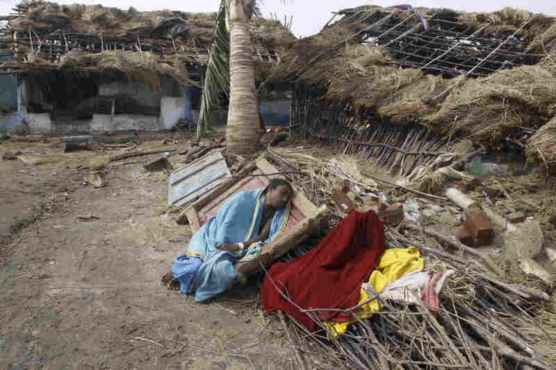 A woman rests near her damaged house after returning to the cyclone-hit Podampeta village on the Bay of Bengal coast.