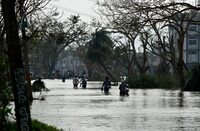 Residents walk through floodwaters Sunday near where Phailin made landfall in Gopalpur a day earlier. Phailin has been blamed for 17 deaths.