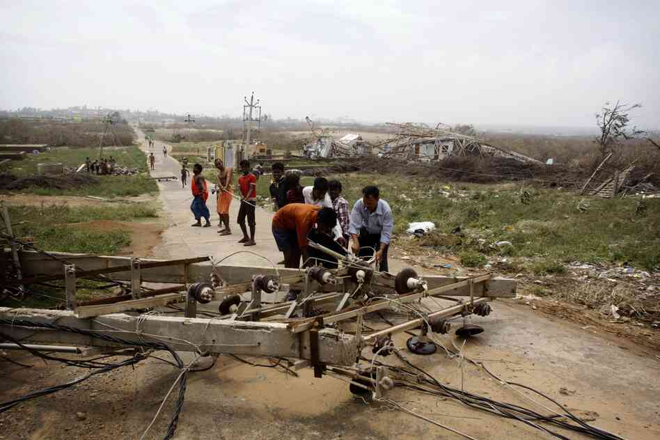 People try to remove an electric pole that fell down in Arjipalli village. Mass evacuations spared India the widespread deaths many had feared from a powerful cyc