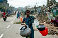An Indian woman carries empty water pots at the fisherman's colony in Gopalpur. Cyclone Phailin left a trail of destruction along India's east coast, but a large evacuation helped minimize casualties.