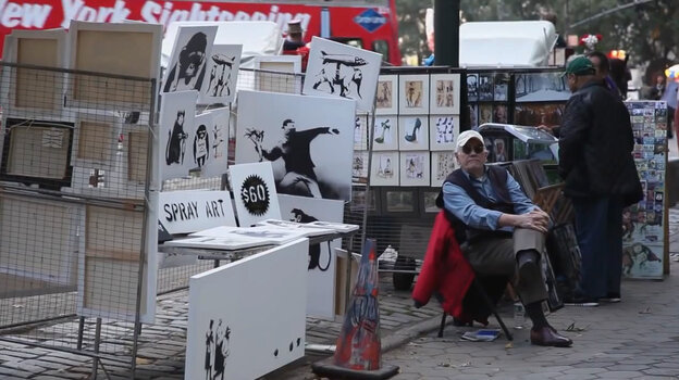 An image from a video posted by Banksy shows a man representing the artist staffing a s