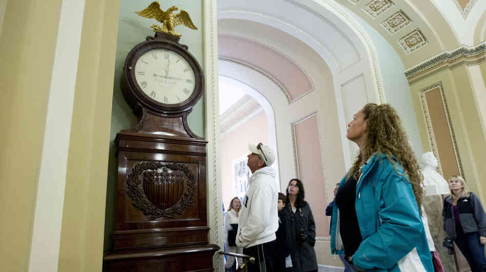 Still Right Twice A Day: Visitors look at the Ohio Clock outside the Senate chamber on Capitol Hill Sunday. The clock that has stood watch over the Senate for 196 years stopped running shortly after noon Wednesday. Employees who wind the clock weekly were furloughed in the federal shutdown.