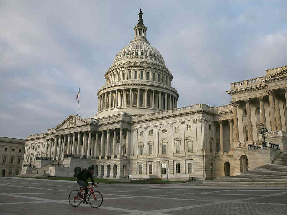 A biker rides past the U.S. Capitol on Monday. Lawmakers are negotiating over plans to raise the federal debt ceiling amid warnings that the government soon won't be able to pay its debts in full.